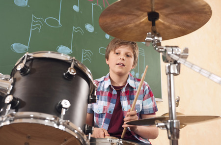 Boy playing drums at music class
