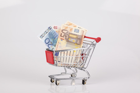 Toy shopping cart filled with euro notes on white background