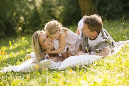 Young family relaxing in garden
