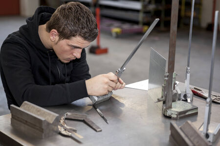 Trainee in workshop working on piece of metal