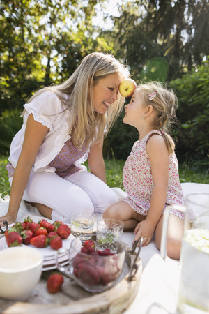 Mother and daughter having picnic in garden