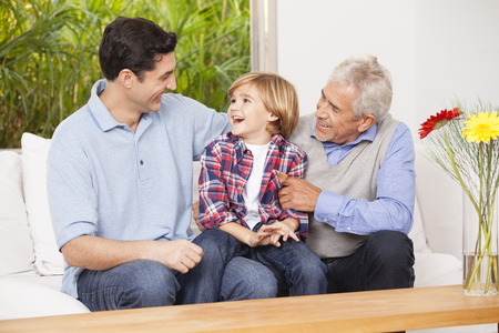 Grandfather, father and son at home together