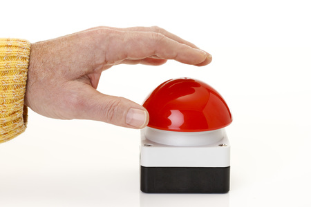 Hand pressing red game show buzzer