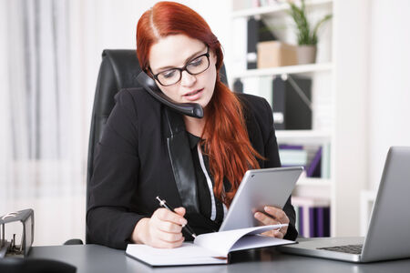 Young businesswoman calling and writing in personal organizer