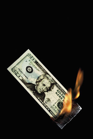 20 dollar note burning against black background