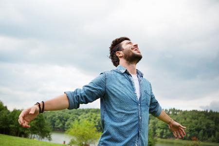Photo pour Emotional young man laughing in wind - image libre de droit