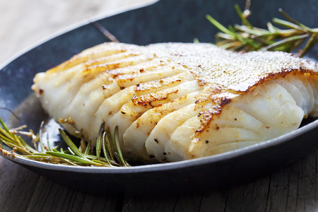Foto de Fried fish fillet, Atlantic cod with rosemary in pan - Imagen libre de derechos