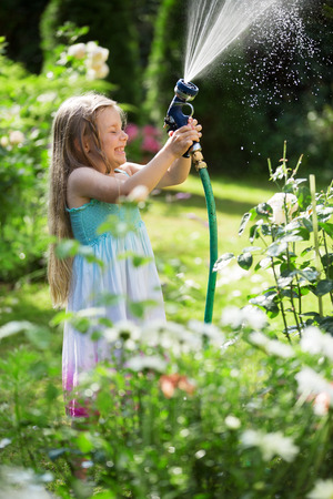 Girl watering plants with garden hose