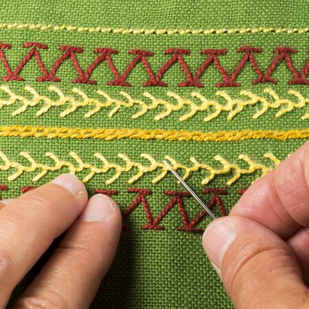 Embroidery, finger holding sewing needle, green linen
