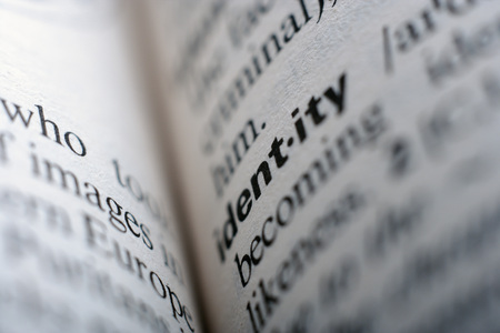 Extreme close up of english dictionary page with word identity