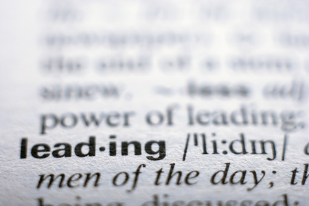 Extreme close up of english dictionary page with word leading