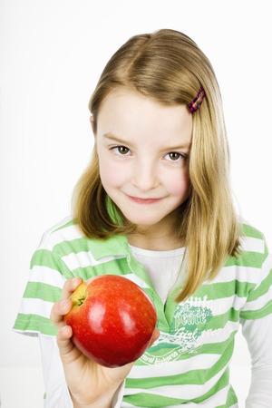 Girl holding apple against white background,smiling,portrait