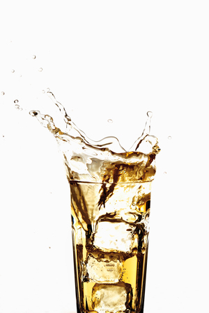 Glass of apple spritzer with ice cubes, close-up