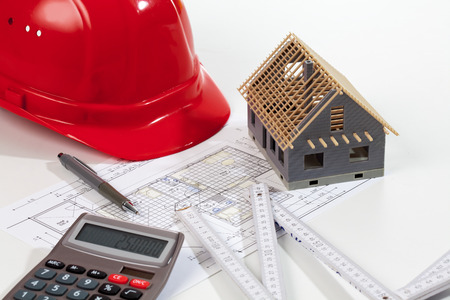 Model house folding ruler calculator hard hat pen on blueprint