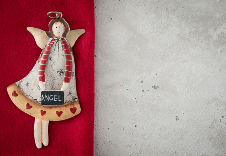 Christmas decoration, angel on red loden, concrete, copy space
