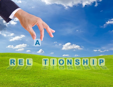Photo pour business man hand and relationship word buttons on green grass meadow - image libre de droit