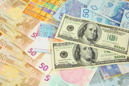 World finance and foreign currency exchange concept - money background with US dollars, Swiss franks, Polish zloty, Euros and Malaysian ringgit.