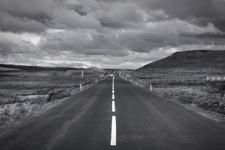 Straight road in Iceland. Volcanic area of Krafla. Vanishing point. Black and white tone - retro monochrome color style.