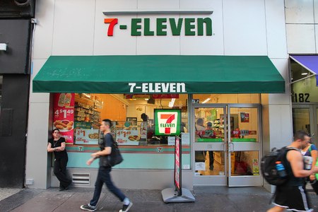 Photo pour NEW YORK, USA - JULY 3, 2013: People walk past 7-Eleven convenience store in New York. 7-Eleven is world's largest operator, franchisor and licensor of convenience stores, with more than 46,000 shops. - image libre de droit
