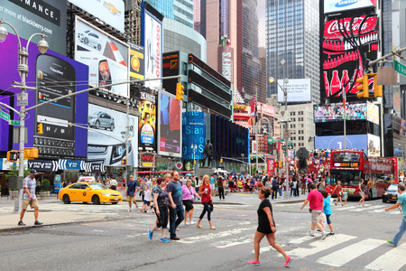 NEW YORK, USA - JULY 4, 2013: Tourists and local people visit Times Square in New York. The square at junction of Broadway and 7th Avenue has some 39 million visitors anually.