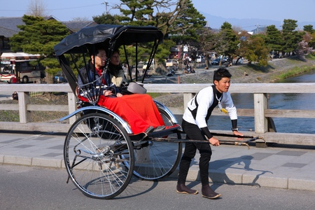 KYOTO, JAPAN - APRIL 17, 2012: Visitors ride a rickshaw in Arashiyama, Kyoto, Japan. Arashiyama is a nationally-designated Place of Scenic Beauty and Historic Site.