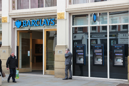 MANCHESTER, UK - APRIL 23, 2013: People walk by Barclays Bank branch in Manchester, UK. Barclays is a multinational finance and banking group based in London, United Kingdom.