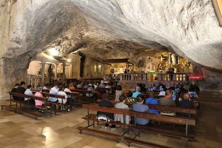 MONTE SANT ANGELO, ITALY - JUNE 6, 2017: People visit the cave church in Monte Sant, Angelo, Italy. The sanctuary town is part of UNESCO World Heritage Site: Longobards Places of Power.