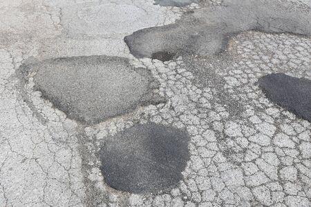 Road surface damage - bad maintenance quality. Asphalt cracks in Italy.