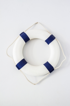 white and blue lifebuoy hanging on white wall
