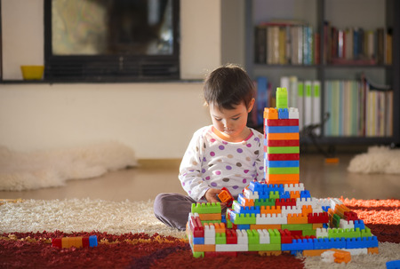 Photo pour Lovely laughing little child, brunette girl of preschool age playing with colorful blocks sitting on a floor in a sunny room with a big window at home or kindergarten - image libre de droit