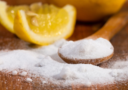 baking soda (sodium bicarbonate) in a wooden spoon and lemon
