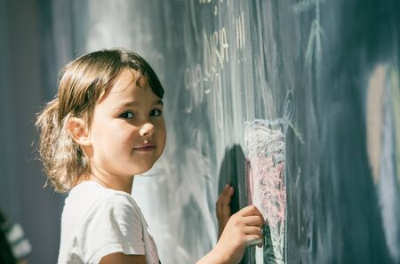 Photo pour Beautiful little girl drawing on a blackboard at playground - image libre de droit