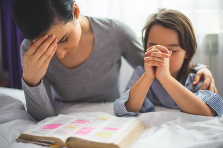 Photo pour Mother and her daughter reading from bible and praying in their knees near the bed - image libre de droit