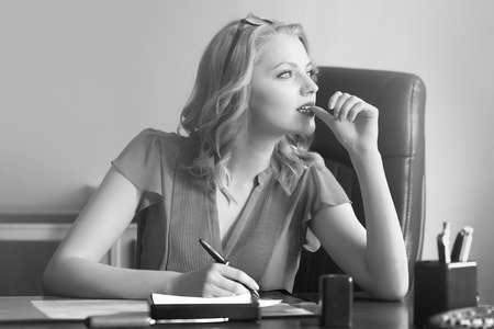 Beautiful young elegant smart business woman sitting in office on leather chair in blouse and glasses holding pen in hands thinking and writing looking away indoor black and white, horizontal picture
