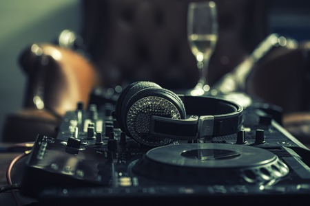 Dj musical mixer professional black console with many buttons and knobs and glamour headphones with pastes in night club or studio on brown leather sofa and wine glass background, horizontal picture
