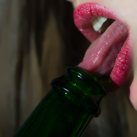 Closeup view of female facial body part of sexual lips with bright red lipgloss licking with tongue in open mouth green color glass wine bottle on blurred background, square picture