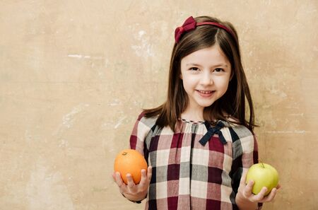 Happy, small, little girl with adorable smile and long, brunette hair smiling with orange and yellow apple, vitamin fruit, in hands on beige wall. Healthy food and diet, copy space