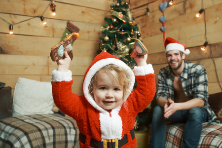 New year small boy son and man. Xmas party celebration, fathers day. Christmas happy child and father with gift on wooden background. Winter holiday. Santa claus kid and bearded man at Christmas tree.