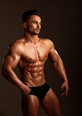 Athletic bodybuilder man on black background. Coach sportsman with bare chest in pants. Man with muscular body and torso. Dieting and fitness. Sport and workout.