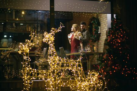 Happy family celebrate new year and christmas. Holidays celebration concept. Couple in love enjoy xmas cuisine, food, wine. Woman and man in restaurant with festive decorations. Winter season romance.