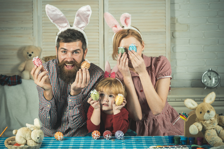 Happy easter family paint eggs. Father, mother and son paint handmade egg. Easter, mother, father and child in bunny ears. Family values, childhood, art. Happy family celebrate spring holiday, love.