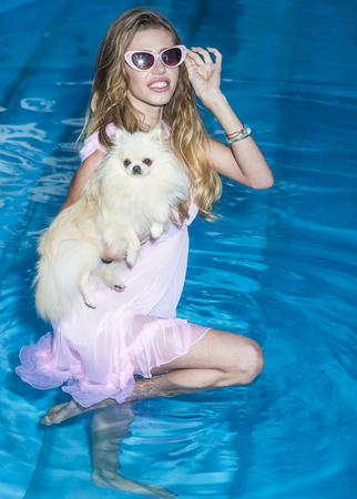 Girl with small dog in swimming pool. Sensual woman with cute spitz puppy in blue water. Pet, companion, friend, friendship. Fashion, beauty, look. Vacation, recreation, spa, wellness.