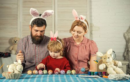 Easter, mother, father and child in bunny ears. Father, mother and son paint handmade egg. Family values, childhood, art. Happy easter family paint eggs. Happy family celebrate spring holiday, love.