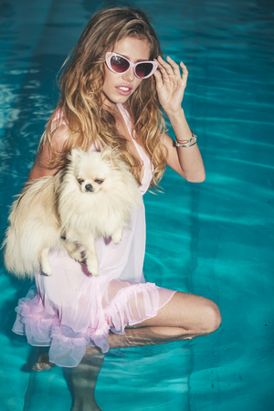 Sensual woman with cute spitz puppy in blue water. Girl with small dog in swimming pool. Pet, companion, friend, friendship. Fashion, beauty, look. Vacation, recreation, spa, wellness.
