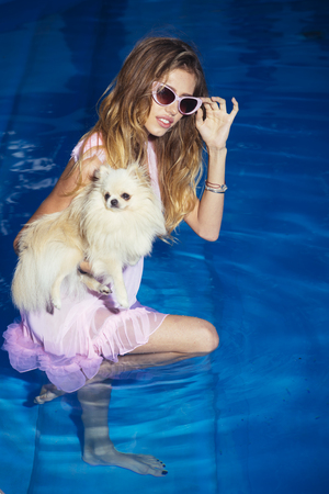 Pet, companion, friend, friendship. Girl with small dog in swimming pool. Sensual woman with cute spitz puppy in blue water. Fashion, beauty, look. Vacation, recreation, spa, wellness.
