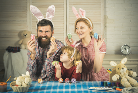 Father, mother and son paint handmade egg. Happy family celebrate spring holiday, love. Happy easter family paint eggs. Family values, childhood, art. Easter, mother, father and child in bunny ears.
