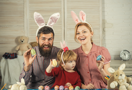 Family values, childhood, art. Happy family celebrate spring holiday, love. Easter, mother, father and child in bunny ears. Father, mother and son paint handmade egg. Happy easter family paint eggs.