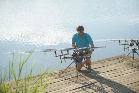 Man fix fishing equipment on wooden pier. Fisherman with spinning rods, reels at freshwater. Summer vacation, adventure, activity. Fishing, angling, hobby, sport, recreation