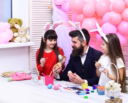 Father and daughters paint handmade egg. Easter, father and children in pink bunny ears. Happy family celebrate spring holiday, love. Happy easter family paint eggs. Family values, childhood, art.