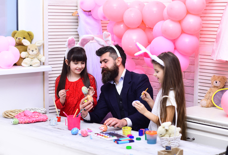 Family values, childhood, art. Father and daughters paint handmade egg. Happy easter family paint eggs. Easter, father and children in pink bunny ears. Happy family celebrate spring holiday, love.